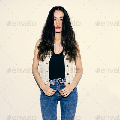 Brunette Model in fashion jeans outfit. Casual fashion