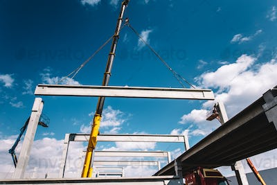 Industrial construction site with heavy duty high crane using prefabricated cement pillars