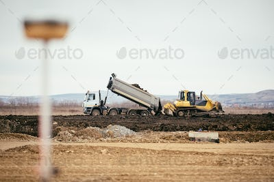 highway construction site development with dumper truck dumping earth