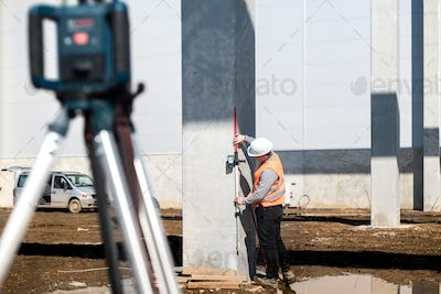 Industrial surveyor on construction site, working with thodolite, gps system and level machine