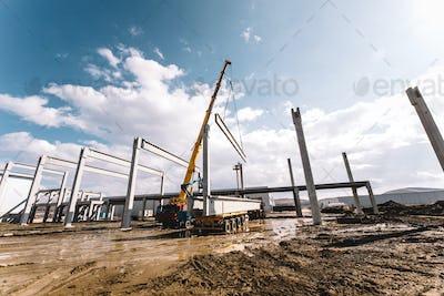 Details of construction site with crane lifting prefabricated concrete framework