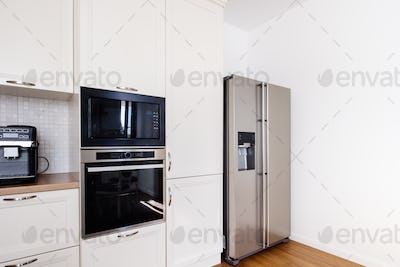 Modern kitchen area, wooden floor with modern refrigerator and appliances