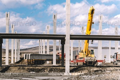 Industrial construction site with prefabricated concrete pillars, heavy duty crane, cargo and trucks