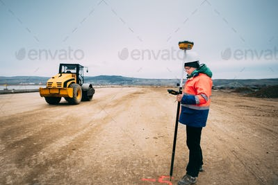 Portrait of engineer on construction site, surveyor using gps system