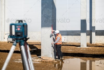 Professional surveyor using gps system and theodolite for correct level on construction site