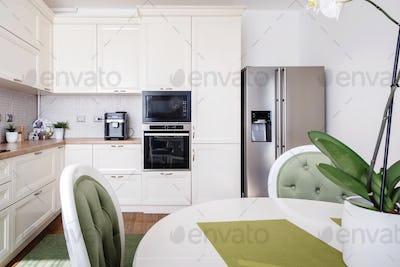 Modern kitchen area and wooden floor with modern refrigerator