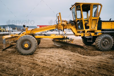 Industry details  - construction site yellow bulldozer levelling and moving soil