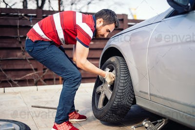 Potrait of young man changing seasonal tires, installing summer tires on automobile