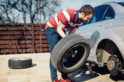 Changing a flat car tire in the backyard.