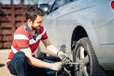 Smiling man and mechanic changing tyres, using jack and wheel wrench