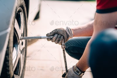Details of mechanic changing tires, working in workshop and making repairs on automobiles