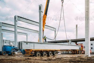 Installation process of prefabricated concrete beams on precast pillars. Industrial crane working