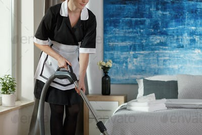 Housemaid vacuuming bedroom