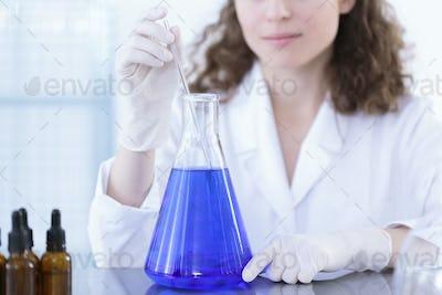 Technician adding sample to flask