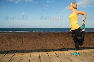 Woman runner stretching at the seaside on sunny summer day