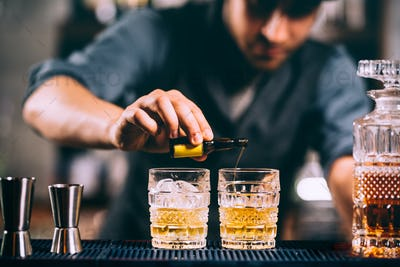 Barman adding cocktail incredients on whiskey cocktails on bar counter