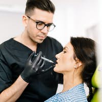 Professional doctor performing lip surgery using hyaluronic acid