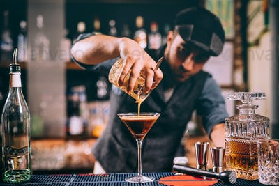 Vintage portrait of bartender creating cocktails at bar. Close up of alcoholic beverage preparation