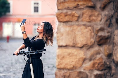 Attractive young woman taking selfie on city streets. Portrait of young woman making faces at camera