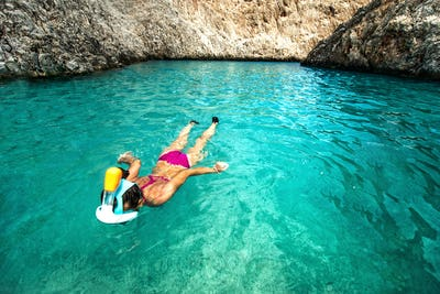 Woman enjoying snorkeling on a sunny day  on remote tropical island