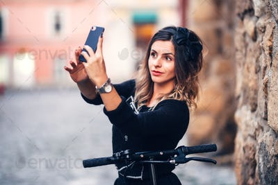 Beautiful young woman taking selfies on city streets