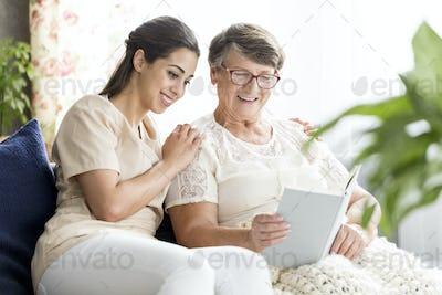 Senior woman and nurse reading