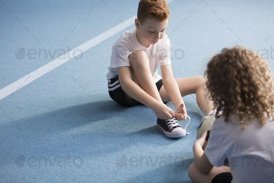 Young boy tying shoelaces
