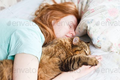 Young redhair woman sleeping with cat