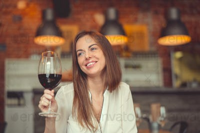 Smiling girl with a glass of red wine