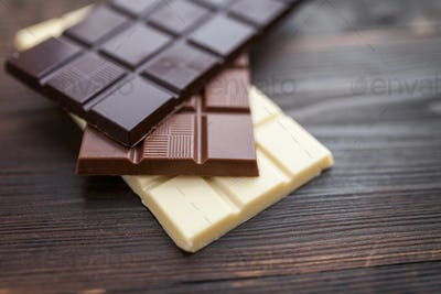 Delicious chocolate bars on wooden background