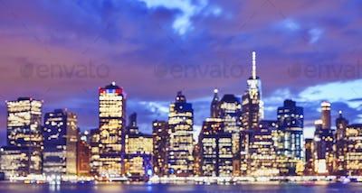 Blurred color toned Manhattan skyline at night, New York.