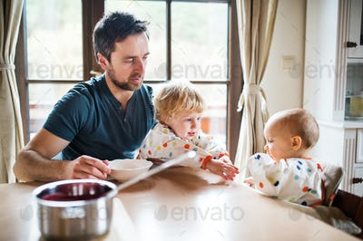 Father feeding two toddlers at home.