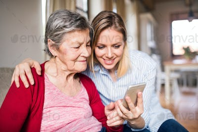 Elderly grandmother and adult granddaughter with smartphone at home.