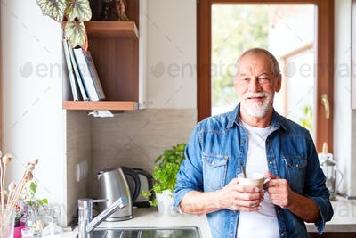 Senior man holding a cup of coffee in the kitchen.