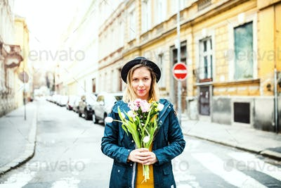Young woman with flowers in sunny spring town.