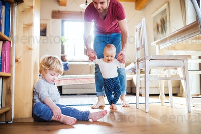 Father with two toddlers at home. First steps.