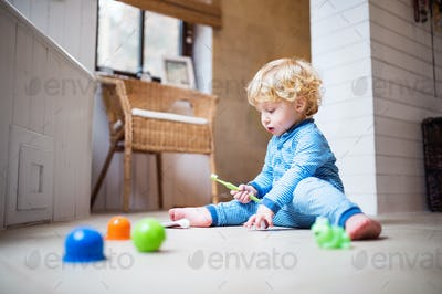 Toddler boy with toothbrush sitting on the floor in the bathroom.