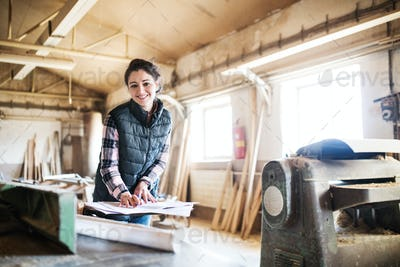Portrait of a woman worker in the carpentry workshop.