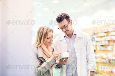 Male pharmacist serving a female customer.