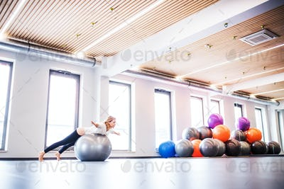 Young woman doing exercise with a fitball in a gym.