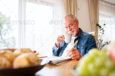 Senior man eating breakfast and doing crosswords at home.