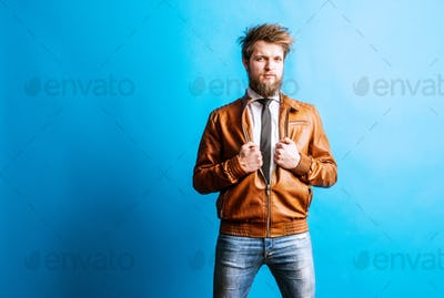 Portrait of a young hipster man in a studio on a blue background. Copy space.