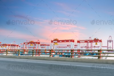 container terminal with highway against a sunset glow sky