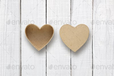 Empty box with cover in shape of heart on white wooden table