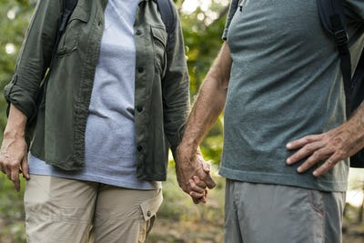 Elderly couple holding hands in the forest