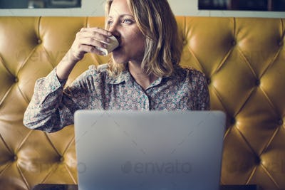 Blond woman working on her laptop at a cafe