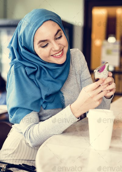 Islamic woman using using smart phone and smiling
