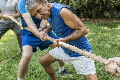 Mature people in tug of war