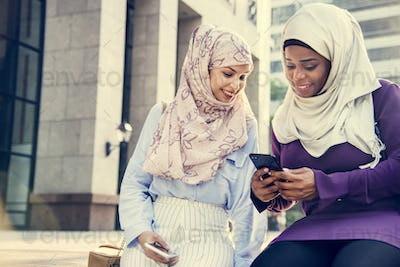 Islamic friends looking at the phone and smiling