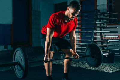 Cross training. Male athlete lifting weights